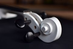 Schließen Sie oben von einer weißen Violinenrolle mit schwarzem pegbox auf undeutlichem Hintergrund stockbilder