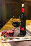 Schließen Sie oben von einer Zusammensetzung - Glas und Flasche Wein und Blumen und Blätter auf einer Tabelle verzieren Stockfotos