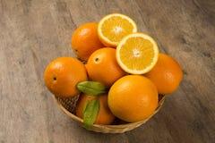 Schließen Sie oben von einigen Orangen in einem Korb über einer Holzoberfläche Stockfotos