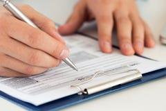 Schließen Sie oben von füllendem Steuerformular des männlichen Buchhalters Stockbilder