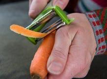 Schließen Sie oben von Frau ` s Händen, die Karotten abziehen Lizenzfreies Stockbild