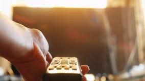 Schließen Sie oben von Frau ` s Hand mit einer Fernsehfernbedienung zur Sonnenuntergangzeit Lizenzfreie Stockfotos