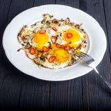 Schließen Sie oben von gebratenen Eiern mit Zwiebel und Paprikas Stockfotos