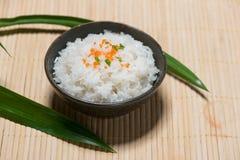 Schließen Sie oben von gekochtem Reis in hölzernem in der Schüssel auf Holztisch Stockbild