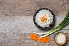 Schließen Sie oben von gekochtem Reis in hölzernem in der Schüssel auf Holztisch Lizenzfreie Stockfotos