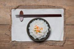 Schließen Sie oben von gekochtem Reis in hölzernem in der Schüssel auf Holztisch Stockfotografie