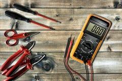 Schließen Sie oben von oben genanntem von Arbeitswerkzeugen auf elektrischen Installationen, auf einem antiken Holztisch lizenzfreies stockfoto