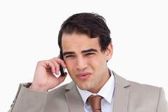 Schließen Sie oben von gestörtem Verkäufer auf seinem Mobiltelefon lizenzfreies stockfoto