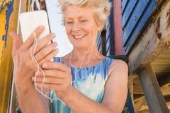 Schließen Sie oben von hörender Musik der glücklichen älteren Frau am intelligenten Telefon lizenzfreie stockfotos