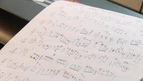 Schließen Sie oben von handgeschriebenen Musikjazzanmerkungen nahe Klavierschlüsseln stock video footage