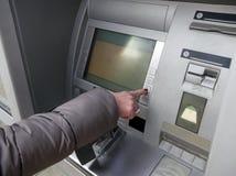 Schließen Sie oben von Handhereinkommendem Stift an einem ATM Weibliche Arme, ATM - hereinkommender Stift Frau, die Bankwesenmasc Lizenzfreies Stockfoto