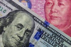 Schließen Sie oben von hundert Dollarbanknote über einer 100 Yuan Banknote mit Fokus auf Porträts von Benjamin Franklin und von M Lizenzfreie Stockfotografie