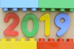 Schließen Sie oben von Jahr 2019 in den bunten Plastikzahlen, die durch Plastikbauklötze umgeben werden Lizenzfreie Stockfotografie