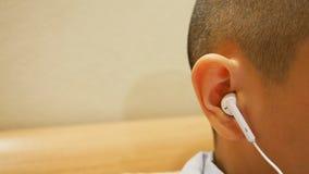 Schließen Sie oben von Junge ` s Ohr unter Verwendung des Kopfhörers lizenzfreies stockbild