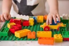 Schließen Sie oben von Kind-` s Händen, die mit bunten Plastikziegelsteinen am Tisch spielen lizenzfreie stockfotografie