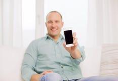 Schließen Sie oben von lächelndem Mann mit Smartphone zu Hause Lizenzfreie Stockfotos