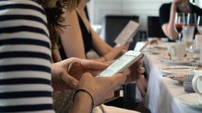 Schließen Sie oben von Mädchen zwei am Café unter Verwendung Smartphones stock video
