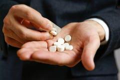 Schließen Sie oben von Mann ` s Hand, die Pillen von der Blisterpackung herausnimmt Stockfotografie