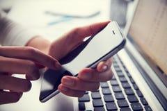 Schließen Sie oben von Person At Laptop Using Mobile-Telefon Stockfotografie
