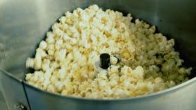 Schließen Sie oben von rührendem Popcorn in der Schüssel auf der Fabrik 4K stock video footage