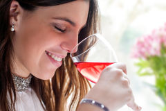 Schließen Sie oben von riechendem Wein des Mädchens lizenzfreies stockfoto