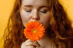 Schließen Sie oben von riechender Blume der schönen Rothaarigefrau über gelbem Hintergrund lizenzfreies stockfoto