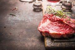 Schließen Sie oben von rohem Frischfleisch Ribeye-Steak mit Kräutern und Gewürzen auf dunklem rustikalem Metallhintergrund Stockfotografie