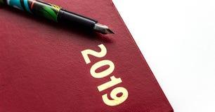 Schließen Sie oben von rotem ledernem Tagebuch 2019 mit Füllfederhalter auf weißem Hintergrund stockfotos