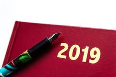 Schließen Sie oben von rotem ledernem Tagebuch 2019 mit Füllfederhalter auf weißem Hintergrund lizenzfreie stockfotos