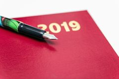 Schließen Sie oben von 2019 roten ledernen diarys mit Füllfederhalter auf weißem Hintergrund stockfotografie