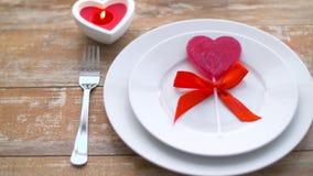 Schließen Sie oben von rotes Herz geformtem Lutscher auf Platte stock video