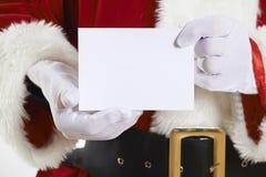 Schließen Sie oben von Santa Claus Holding Blank Invitation Stockfoto