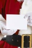 Schließen Sie oben von Santa Claus Holding Blank Invitation stockbilder