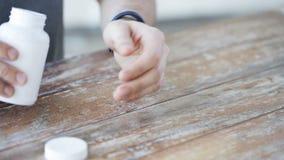 Schließen Sie oben von strömenden Pillen des Mannes von Glas zu Hand stock video footage