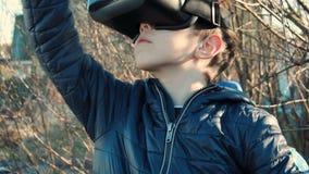 Schließen Sie oben von tragendem Kopfhörer der virtuellen Realität des Jungen im Hinterhof seines Hauses stock footage