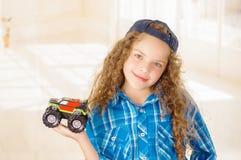 Schließen Sie oben von tragender Jungenkleidung des schönen gelockten Mädchens mit Hut und dem Halten eines Autospielzeugs in ihr stockfotografie