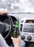 Schließen Sie oben von trinkendem Alkohol des Mannes beim Fahren des Autos Lizenzfreie Stockfotos