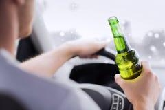 Schließen Sie oben von trinkendem Alkohol des Mannes beim Fahren des Autos Stockbilder