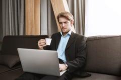 Schließen Sie oben von trinkendem Kaffee des eleganten unrasierten Mannes und im Laptopmonitor mit ernstem und unzufriedenem Ausd Lizenzfreie Stockbilder