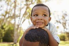 Schließen Sie oben von Vater-Carrying Son On-Schultern, die in Park gehen Lizenzfreie Stockbilder