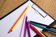 Schließen Sie oben von vielen farbigen zeichnenden Bleistiften und vom Klemmbrett mit blan Stockfotografie