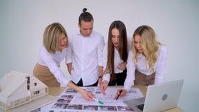 Schließen Sie oben von vier Architekten, die zusammen Plan am Schreibtisch mit Plänen besprechen stock video