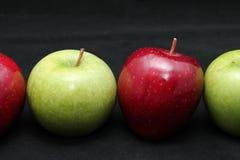 Schließen Sie oben von vier frischen glänzenden grünen und roten Äpfeln auf einem Hintergrund des dunklen Schwarzen Stockfoto