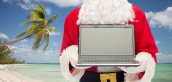 Schließen Sie oben von Weihnachtsmann mit Laptop Stockbild