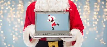 Schließen Sie oben von Weihnachtsmann mit Laptop Stockfoto