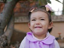 Schließen Sie oben von wenigem asiatischem Baby und in einer guten Laune lächeln und sein stockbild
