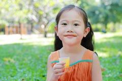 Schließen Sie oben von wenigem Mädchen, das Orangensaft mit befleckt um ihren Mund im Sommergarten trinkt lizenzfreie stockfotografie