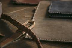 Schließen Sie oben von wenigen handgemachten Geldbeuteln und von umsponnenem Lederband auf Holztisch Lizenzfreies Stockbild