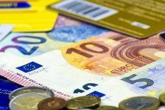 Schließen Sie oben von zerstreuten Banknoten und von einem Zerstreuen von Münzen und von Kreditkarten Banknoten von 5, 10, 20 Eur lizenzfreie stockfotos