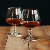 Schließen Sie oben von zwei Glasbechern mit dem Alkohol, der auf einem Holztisch gegen einen dunklen Hintergrund stillsteht lizenzfreie stockfotografie